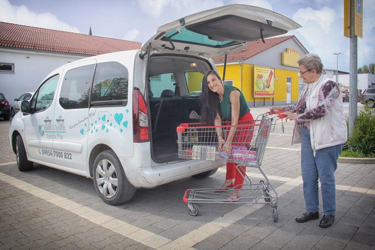 Pflegekraft und Seniorin beim Einkaufen